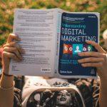 Person reading Digital Marketing book.