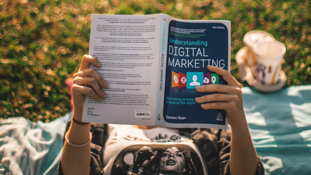 Person reading Digital Marketing book.